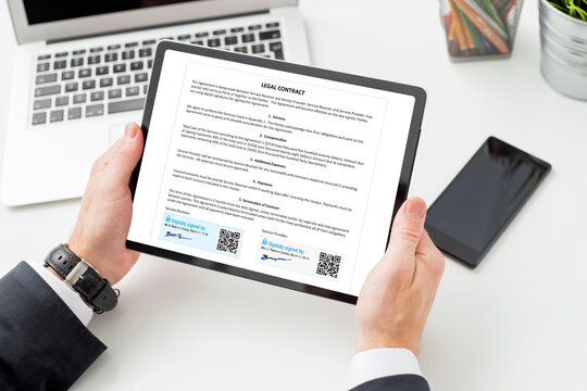 Man at work signing legal contract by using digital signature