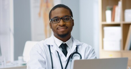 Close up portrait of joyful happy young African American male physician in glasses sitting in...