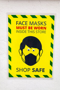 A wall sign stating that face masks must be worn while inside the store. Comedy googly eyes have been stuck on the eyes