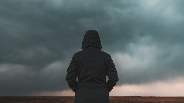 Rear view of female person wearing hooded jacket against dark moody dramatic clouds at sky