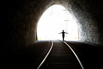 Silhouette of a girl coming out of the tunnel. Light at the end of the tunnel. Stone walls. Railway rails in the foreground. Wall mural