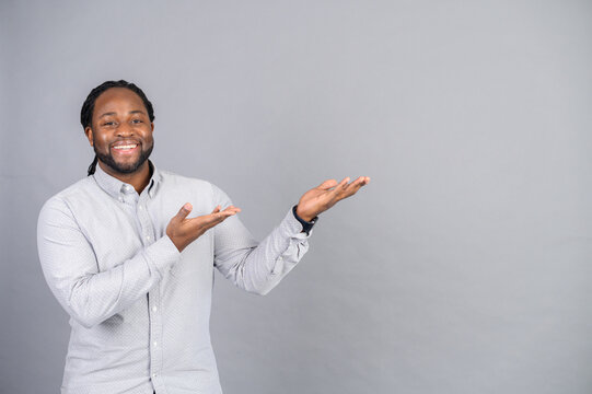 Look at here. African-American guy wearing smart casual shirt is advertising new product, points both hands away at empty copy space, a multiracial guy presents a novelty, isolated on grey