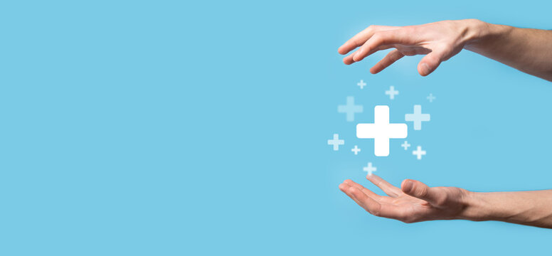 Male hand holding plus icon on blue background. Plus sign virtual means to offer positive thing (like benefits, personal development, social network)Profit,health insurance, growth concepts
