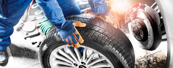 Auto mechanic working in garage and changing wheel alloy tire.