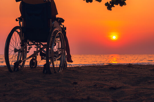 Asian special child on wheelchair on the sea beach with sunset on travel time in holiday family and learning about nature around the sea,Lifestyle in the education age kids,Happy disabled kid concept.