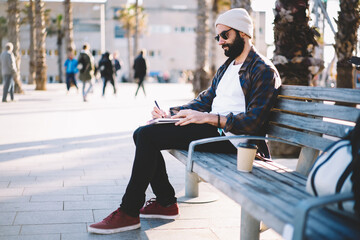 Talented Turkish male poet writing text ideas in copybook for creating articles, Middle Eastern hipster guy in sunglasses spending leisure daytime for note travel impression to personal diary