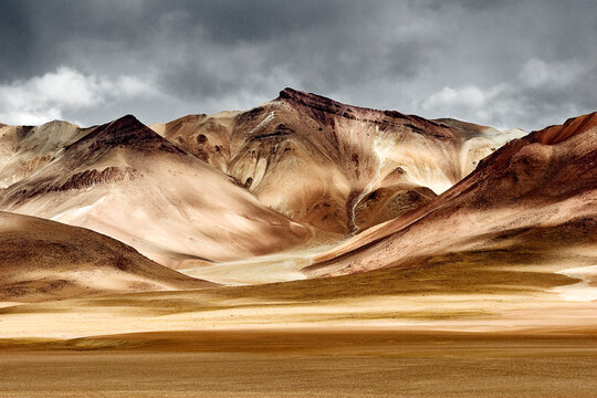 Deserted Landscape Of Mountains With Storm Clouds In The Sky, The Sun Light Created High Contrast