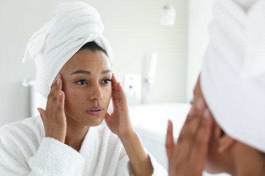 African american woman in bathrobe touching her face while looking in the mirror at bathroom