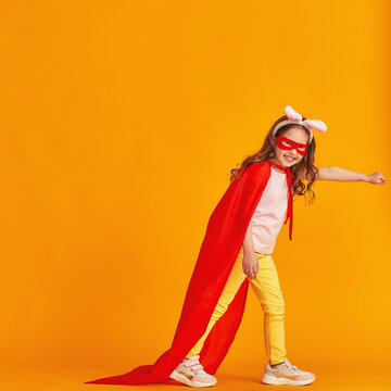fun little girl is playing in superhero costume. baby is dressed in rabbit ears, red cape, mask, holding out her hand on yellow background. concept girl's superpowers, feminism, striving for victory