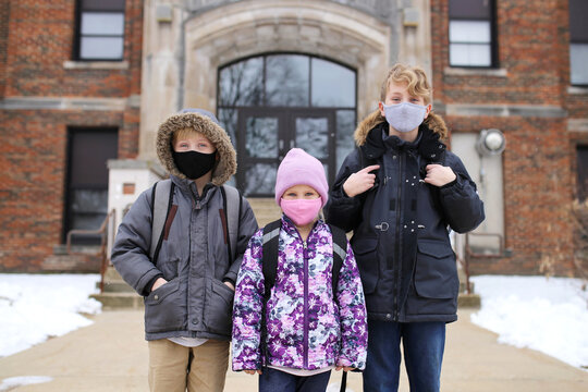 Little Kids Standing in Front of School Building with Protective Covid Masks