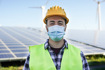 Fototapeta Young man working for renewable energy while wearing safety face mask for coronavirus outbreak - Solar panel station and wind turbines