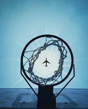 Airplane Flying Against Sky Seen Through Basketball Hoop