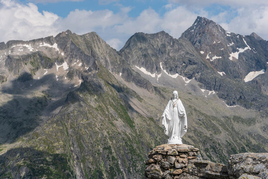 White Statue Of Virgin Mary, Mother Of God, Placed On Top Of The Mountain In Background