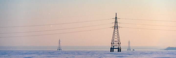 Industrial high voltage electricity tower in snow field at winter. Wide banner