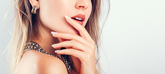 Nail art and design. Beautiful woman wearing make-up and jewellery showing french manicure on white background