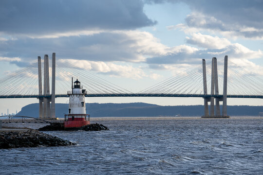 Tarrytown, NY - USA - Mar. 14, 2021: Landscape view of the Tarrytown Light, a sparkplug lighthouse on the east side of the Hudson River. The Mario M. Cuomo Bridge in the distance.