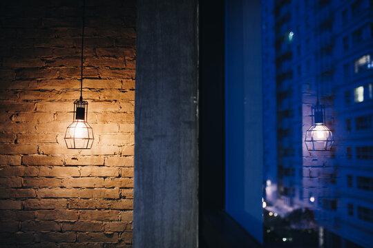 Illuminated Street Light On Wall Of Building At Night