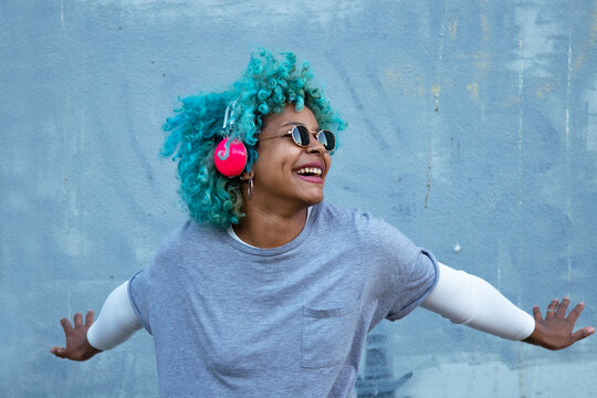 black afro american woman with headphones on the street smiling happy