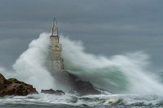 View Of Lighthouse Against Cloudy Sky During Sea Storm.  Huge Waves Hit The Lighthouse.