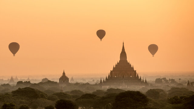 Hot Air Balloons Over Temple Buildings Against Sky