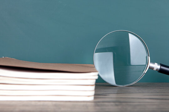 A stack of notebooks and a magnifying glas
