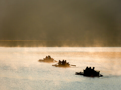 People Ride On Raft, There Is A Lot Of Cold And Fog Floats On Water Surface In Natural Reservoir.