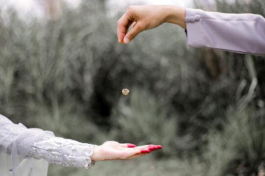 Cropped Image Of Man Throwing Wedding Ring On Bride Hand