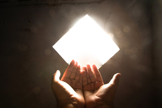 Person Hand Against Illuminated Wall