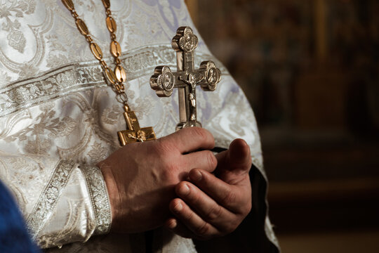 Midsection Of Priest Holding Cross In Church
