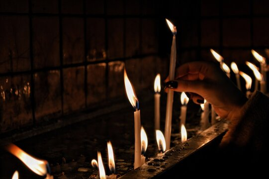 Human Hand Holding Lit Candles In Temple