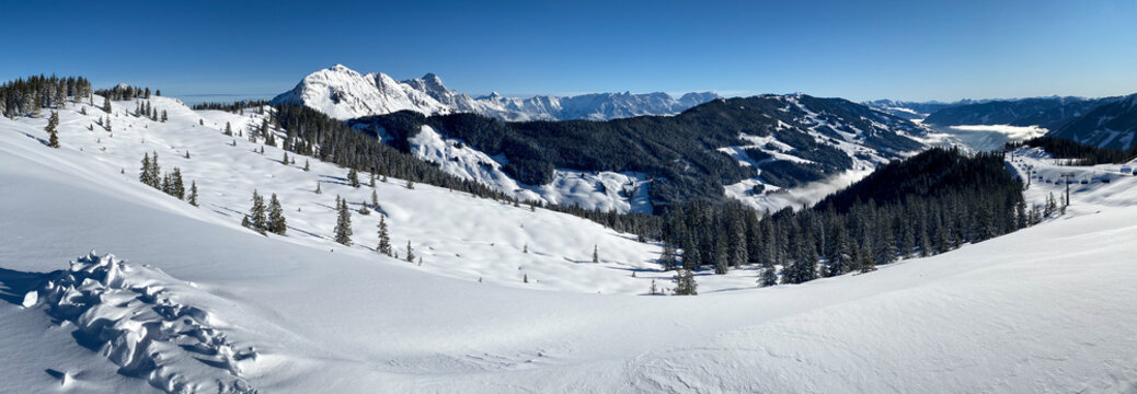 Panorama Of Snow Covered Mountains In Saalbach Hinterglemm In The Austrian Alps Against Blue Sky