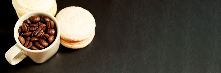 White cup with coffee grain and sweet macaroons on the table. Cafe header and background template