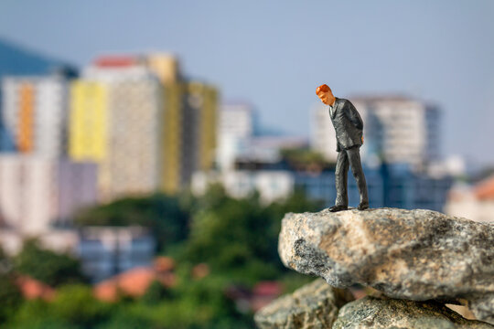 Businessman Standing On The Rock With Building Background