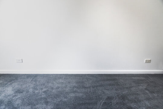 empty room with brand new grey blue carpet laid on the floor and freshly painted white walls, home renovation