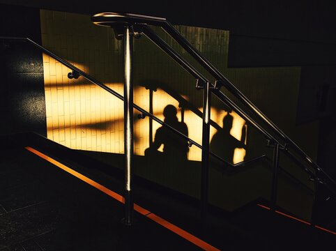 Silhouette Walking On Illuminated Walkway At A Subway Station