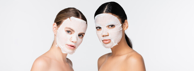 Fototapeta young interracial women in moisturizing sheet masks isolated on white, banner
