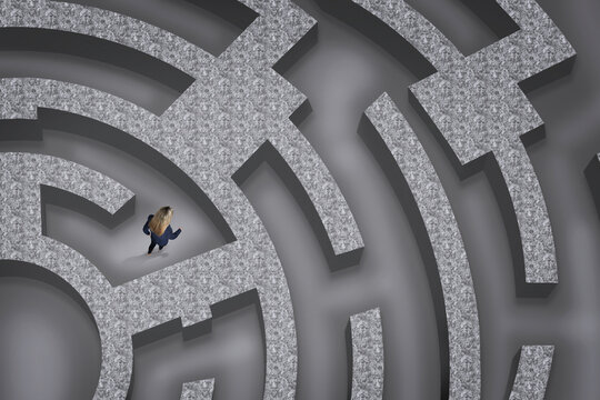 Businesswoman trying to find way out of maze, above view