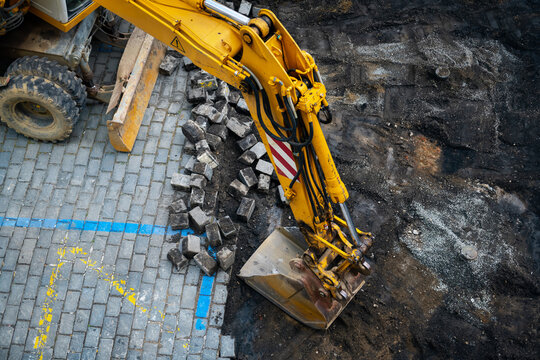 Detail of the excavator working on the cobblestone street reconstruction.