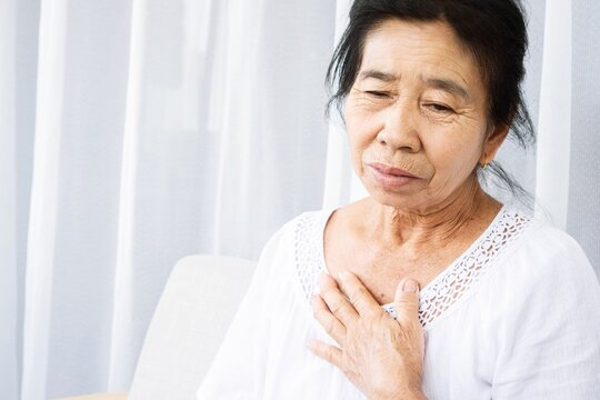 old Asian woman having problem with shortness of breath, difficult breathing hand touching her chest