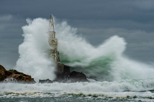 Lighthouse By Sea Against Sky During Severe Sea Storm