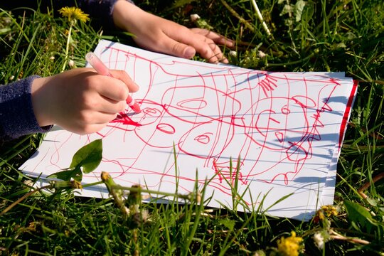 Close Up View Of Child's Hand Drawing Colorful Ornaments On Paper. Notebook In  Grass Of Meadow.