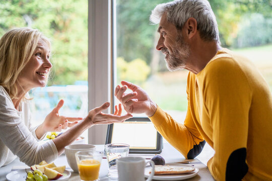 Smiling mature couple talking with each other while having breakfast