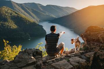 Man relaxing with his dog at a beautiful viewpoint with rocks and lake.