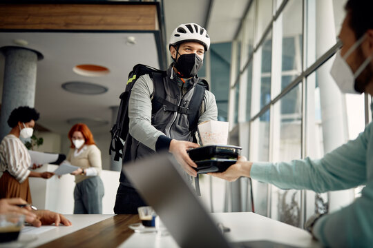 Courier with face mask delivering lunch to businessman who is working at corporate office.