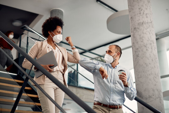 Happy business co-workers wearing face masks and greeting with elbows on staircase of their office building.