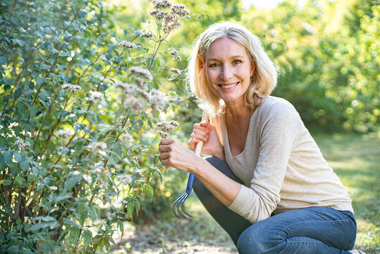 Portrait of smiling mature woman holding flowers in backyard