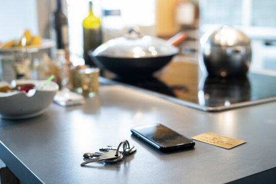 Close-up of smartphone, keys and credit card on kitchen worktop