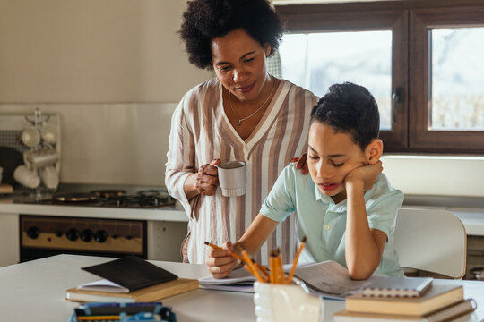 Black mother assisting her son about homework