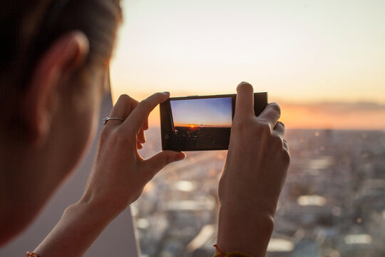 Man Photographing Through Smart Phone Against Sky