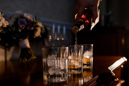 Close up view of man pouring whiskey into glasses. Concept of luxury party.